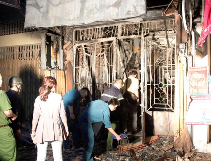 Lực lượng chức năng khám nghiệm hiện trường căn nhà cháy
