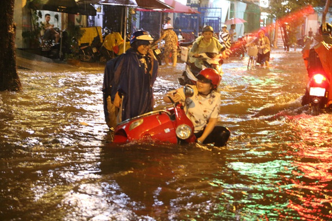 Một người dân té ngã khi lưu thông trong tình trạng mưa ngập - Ảnh: LÊ PHONG