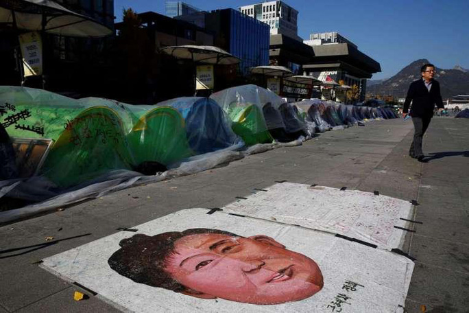Bức tranh vẽ Tổng thống Park trên đất trước lều trại của những người xuống đường đòi bà từ chức. Ảnh: REUTERS, EPA