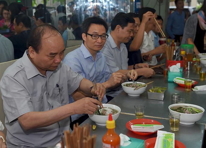 Thủ tướng và đoàn kiểm tra dừng chân, dùng điểm tâm tại một quán ăn đường phố thuộc phường Tân Thành, TPHCM. Ảnh: VGP/Quang Hiếu