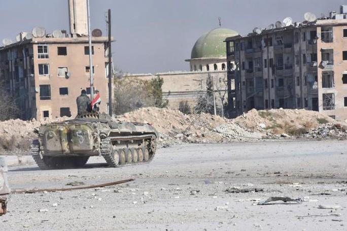 Quân chính phủ Syria xuất hiện gần một nhà thờ Hồi giáo sau khi kiểm soát được khu Al-Haidariya của TP Aleppo (Syria). Ảnh: REUTERS