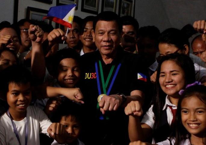 Tổng thống Duterte chụp ảnh cùng trẻ em trong chuyến thăm TP Tarlac ngày 11-12. Ảnh: REUTERS