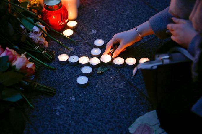 Một phụ nữ thắp nến tưởng niệm nạn nhân trong vụ xe tải lao vào chợ Giáng sinh ở thủ đô Berlin - Đức hôm 19-12. Ảnh: Reuters