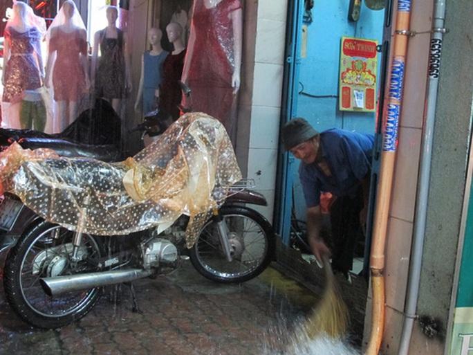 Một người sống trên đường Nguyễn Thị Minh Khai quét nước tràn vào hiên nhà
