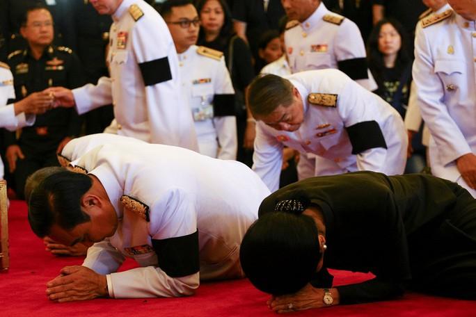 Thủ tướng Chan-o-cha và vợ thực hiện nghi lễ trước di ảnh Quốc vương Bhumibol tại Cung điện Hoàng gia. Ảnh: Reuters.