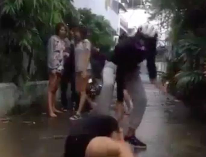 Nhí Tinô (Mặc áo đen) đang đạp vào đầu và đánh một nữ sinh khác ở huyện Nhà Bè (TP HCM)