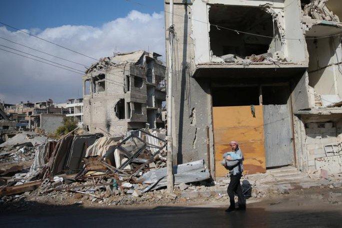 Các tòa nhà bị phá hủy ở TP Douma, phía Đông Damascus ngoại ô Ghouta, Syria hôm 30-12. Ảnh: Reuters