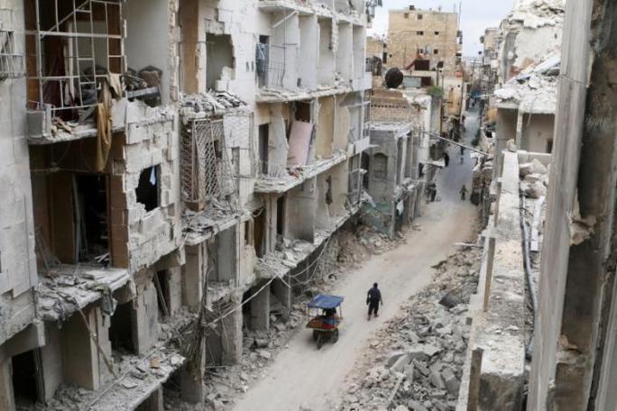 Người dân di chuyển bên những căn nhà bị tàn phá ở Aleppo ngày 5-5-2016. Ảnh: Reuters
