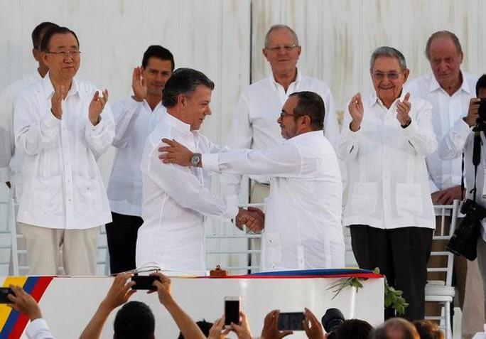 Tổng thống Juan Manuel Santos (trái) và thủ lĩnh phiến quân Timochenko lần đầu tiên bắt tay nhau trên lãnh thổ Colombia. Ảnh: Reuters