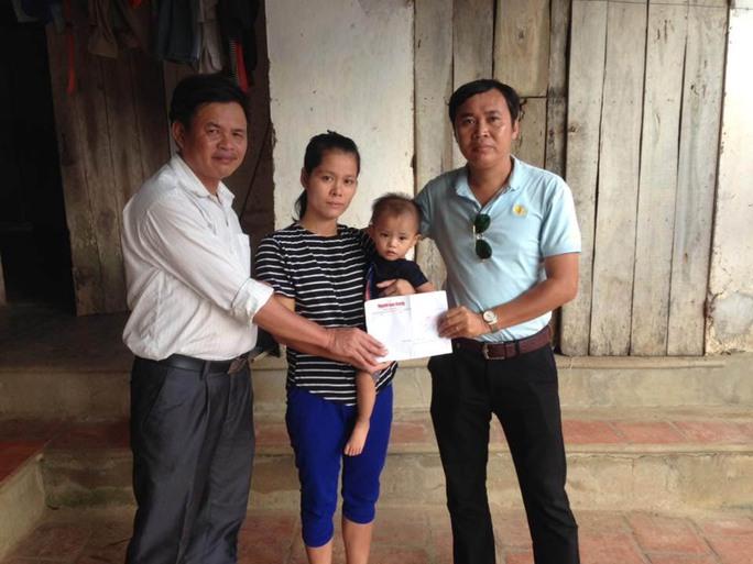 Gia đình bé Nguyễn Cảnh Chính nhận tiền hỗ trợ từ Quỹ Regina do phóng viên Báo Người Lao Động (bìa phải) đến traoẢnh: HẢI VŨ
