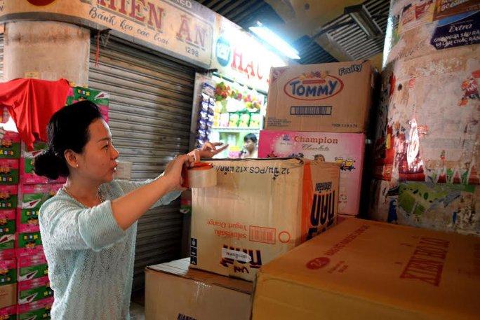 Một số tiểu thương đang gói gém hàng để chuẩn bị dời ra chợ tạm