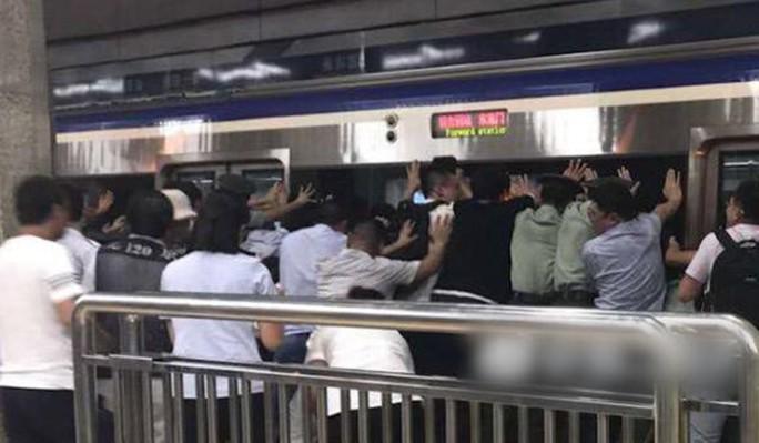 Hàng trăm người đẩy nghiêng tàu điện ngầm, cứu nạn nhân mắc kẹt - Ảnh 3.