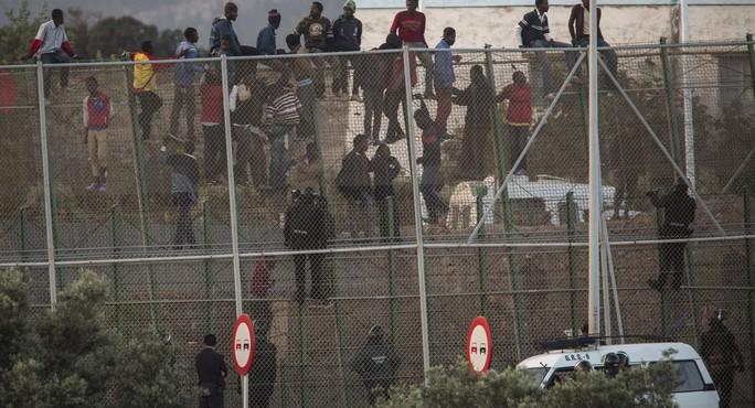 Người di cư trèo qua hàng rào. Ảnh: AP