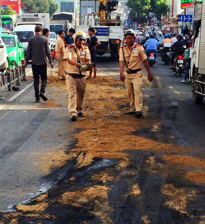 Lực lượng CSGT rải cát lấp dầu nhớt trên đường.