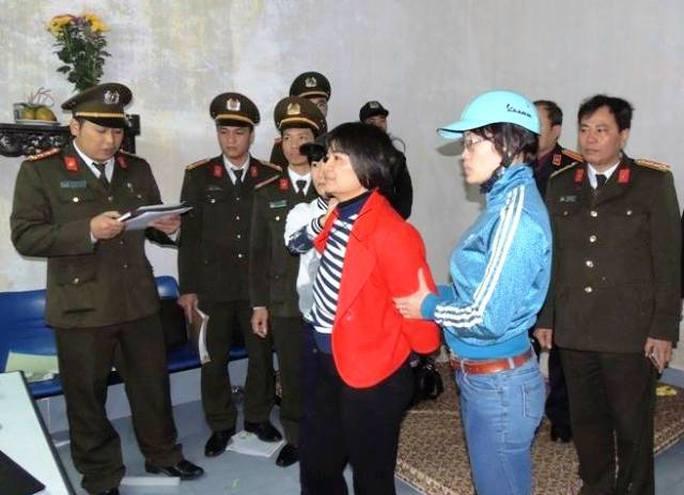 Trần Thị Nga (áo đỏ) đang được Công an tỉnh Hà Nam đọc lệnh thi hành bắt tạm giam