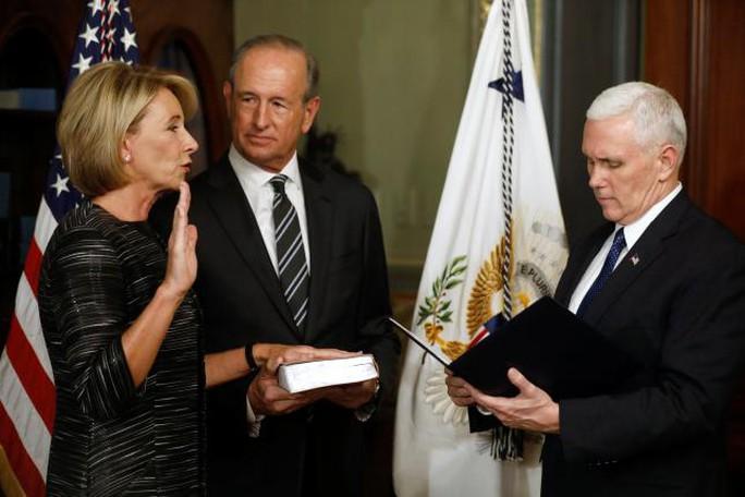 Bà Betsy DeVos (trái) tuyên thệ nhậm chức bộ trưởng giáo dục trước sự chứng kiến của Phó Tổng thống Mike Pence (phải) tại Nhà Trắng hôm 7-2. Ảnh: REUTERS