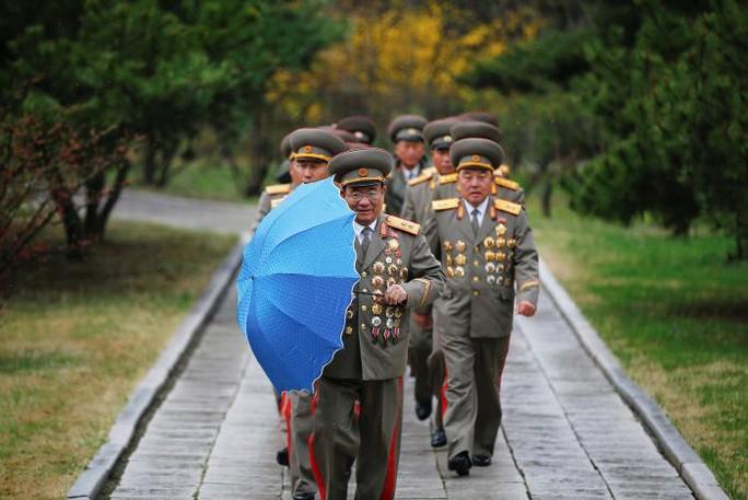Quan chức quân đội Triều Tiên đội mưa tới nơi sinh của cố lãnh tụ Kim Nhật Thành. Ảnh: REUTERS