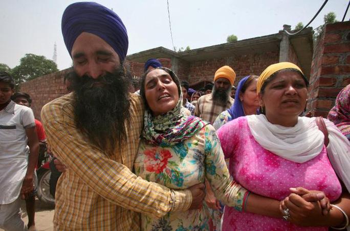 Vợ của binh sĩ Ấn Độ Paramjit Singh (giữa) gần như ngất lịm khi được thông báo chồng cô bị quân đội Pakistan giết chết. Ảnh: REUTERS