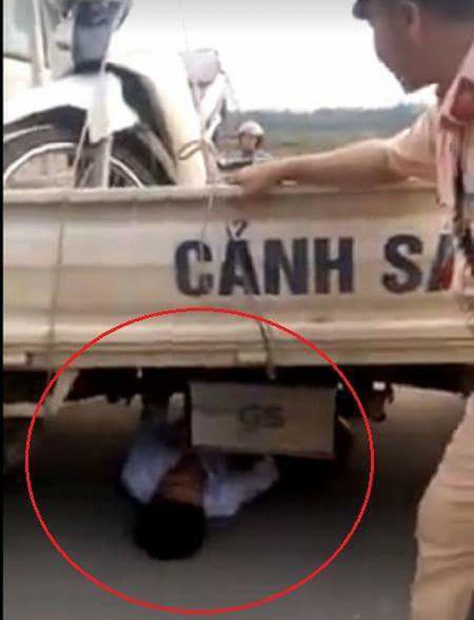 Bị giữ xe, nam thanh niên chui vào gầm ô tô CSGT ăn vạ - Ảnh 1.