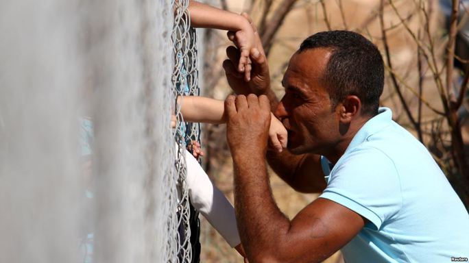 Cảm động nụ hôn qua hàng rào của ông bố tị nạn người Syria - Ảnh 1.