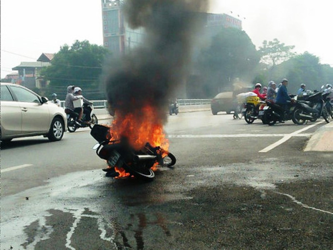 Người phụ nữ và cháu nhỏ tháo chạy khỏi xe máy cháy ngùn ngụt giữa phố - Ảnh 1.
