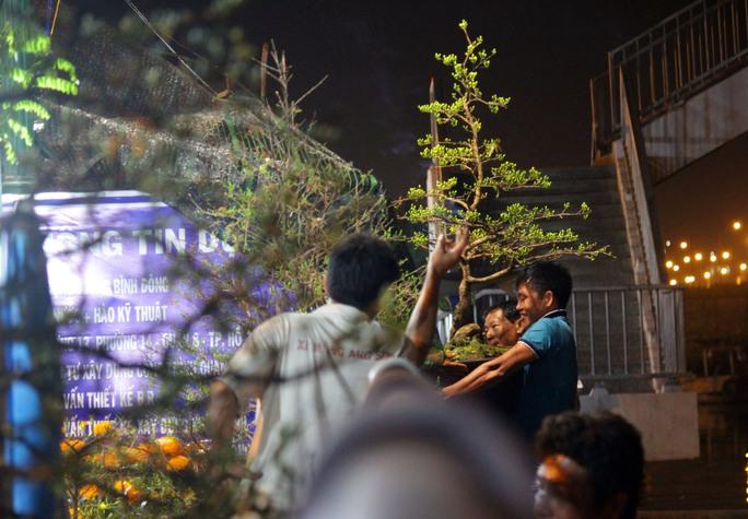 Khoảng 19 giờ ngày 23-1, người dân ghé Bến Bình Đông tham quan và mua hoa, cây cảnh ngày càng đông. Các chủ hàng bận rộn, tất bật di chuyển cây cảnh từ thuyền lên bờ
