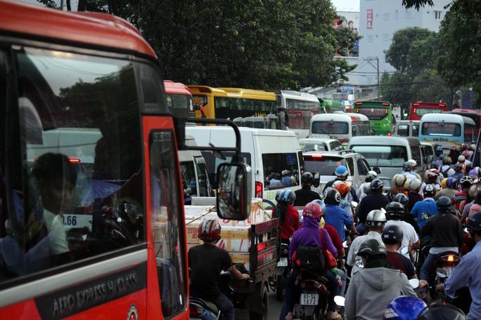 Xe khách và các phương tiện giao thông khác nối đuôi nhau trên đường Đinh Bộ Lĩnh chiều 24-1.