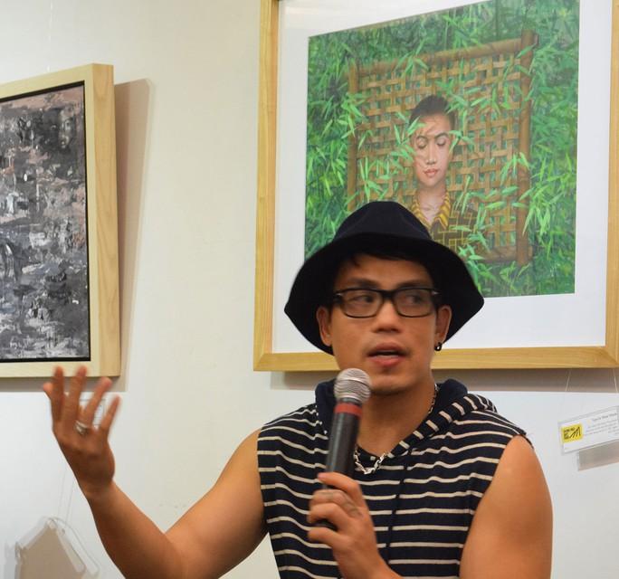 Giám tuyển Như Huy đang giới thiệu tại một cuộc triển lãm tranh