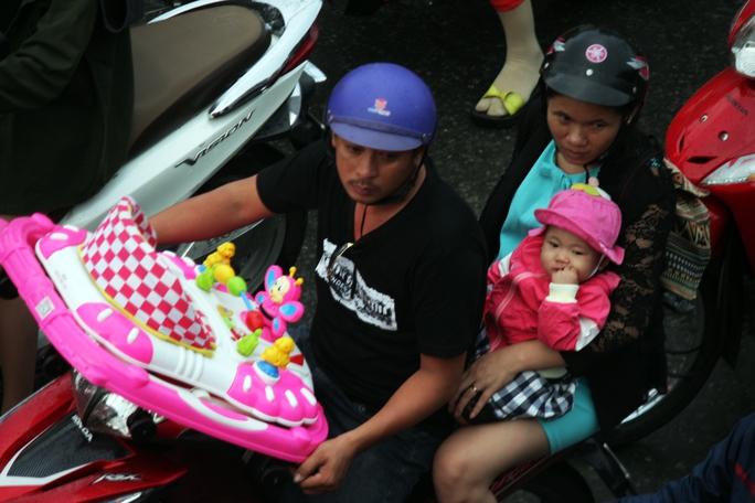 Nhiều em nhỏ mệt mỏi cùng bố mẹ đội mưa, vượt quãng đường đông đúc xe cộ trở về thành phố.