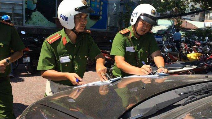 Đoàn liên ngành quận 3 lập biên bản xử lý các ô tô đậu trái phép trên đường Trần Quốc Thảo.