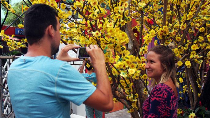 Hai du khách nước ngoài nán lại bên cây hoa mai giả rất lâu để chụp dược những bức hình ưng ý, đúng bản sắc văn hóa Việt Nam.
