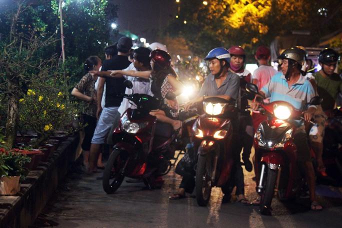Đa số người dân sử dụng xe máy đi dọc Bến Bình Đông rồi dừng lại từng gian hàng để tham quan và lựa chọn hoa Tết về nhà đón năm mới.