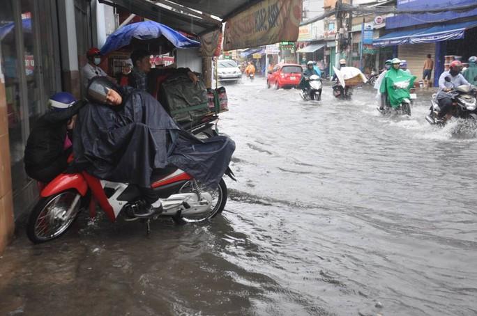 Một người đàn ông tấp xe vào lề đường nghỉ mệt do phải di chuyển trên đường ngập nước