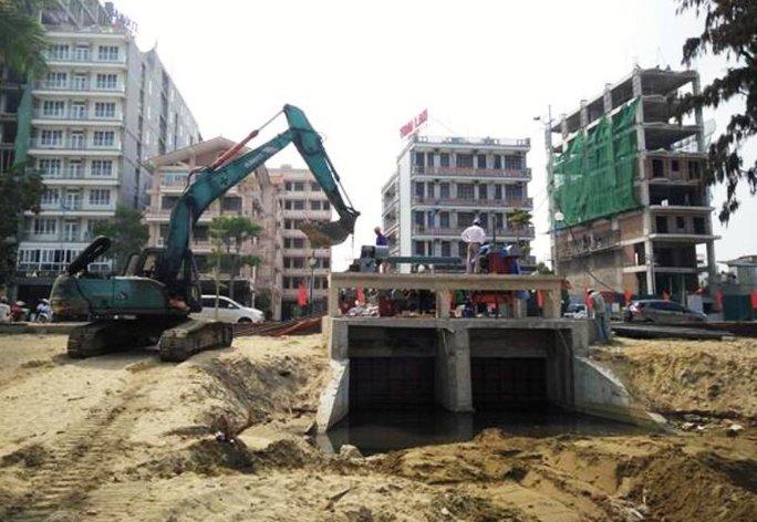Chính quyền Sầm Sơn đang cho xử lý cống nước thải chảy tràn ra bãi biển chiều ngày 3-5