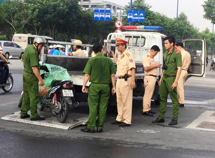 Lực lượng chức năng di dời xe máy của 2 nạn nhân khỏi hiện trường