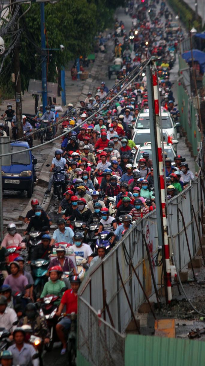 Xe cộ chen nhau chật cứng trên đường Trường Chinh, đoạn rào chắn để xây dựng hầm vượt. Người dân cho biết khu vực này kẹt xe thường xuyên, hôm nay mưa nhưng phần lớn người dân nghỉ lễ chưa lên thành phố nên chưa kẹt nhiều.