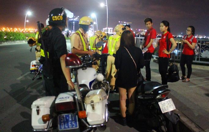 Một tổ công tác đang kiểm tra hành chính nhóm thanh thiếu niên đậu xe, tụ tập trên cầu Thủ Thiêm.