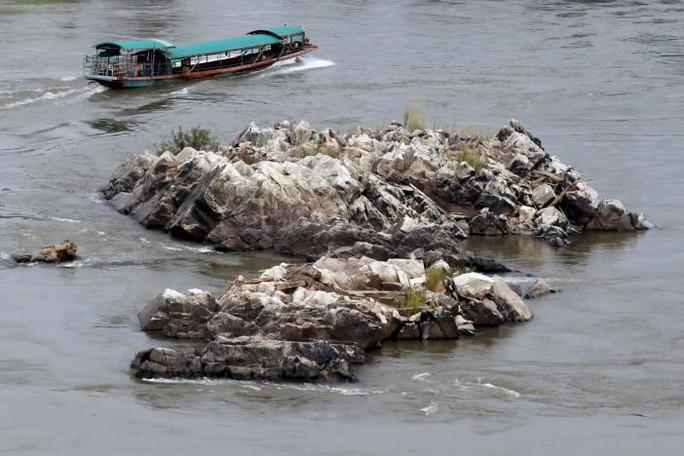 Một chiếc thuyền đi dọc theo các bãi đá ở sông Mekong tại biên giới giữa Lào và Thái Lan ngày 23-4. Ảnh: REUTERS