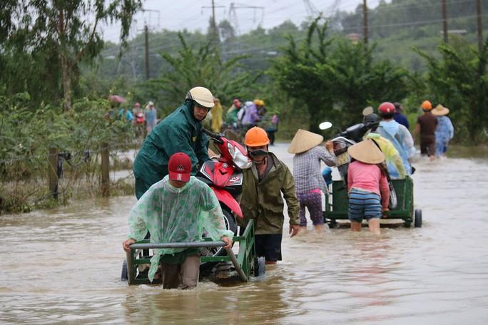 Người dân Quảng Nam dùng xe bò chở xe máy vượt lũ - Ảnh 1.