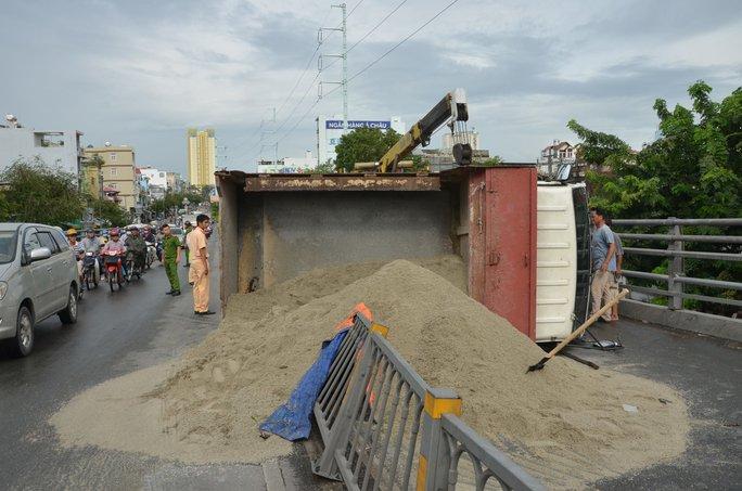 Xe tải lật ngang, cát đổ tràn cầu vượt Cây Gõ - Ảnh 1.