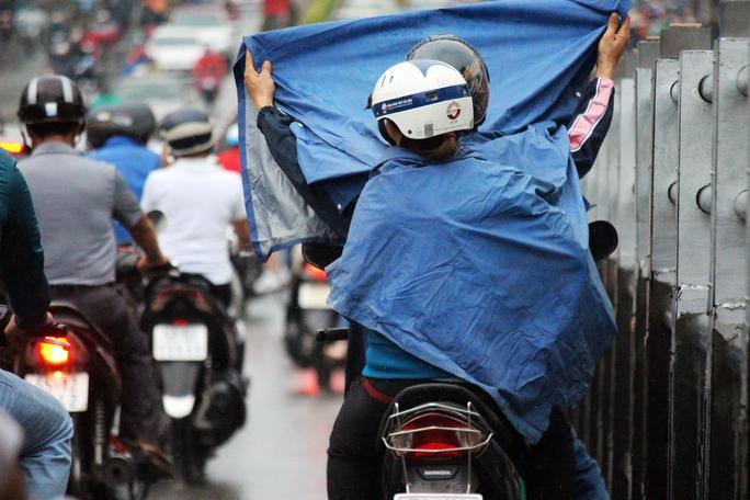 Người đi xe máy dừng trên cầu vượt Hoàng Hoa Thám để mặc áo mưa, cản trở giao thông, góp phần khiến gia tăng ùn ứ.