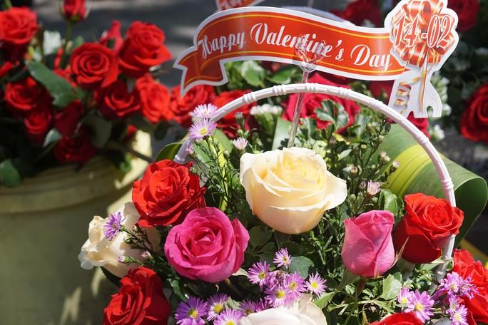 """Trung bình hoa hồng có giá từ 15.000 đồng/bông. Một lẵng hoa được các chủ cửa hàng đầu tư """"trang điểm"""" có giá từ 200.000-250.000 đồng/lẵng."""