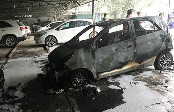 Ô tô bất ngờ bốc cháy ngùn ngụt trong bãi gửi xe - Ảnh 1.