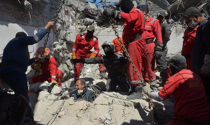 Lực lượng cứu hỏa tìm kiếm thi thể sau một cuộc không kích của liên quân ở Iraq. Ảnh: Reuters