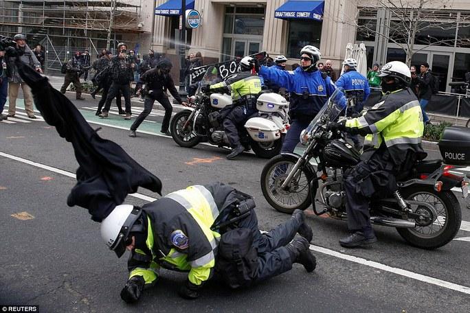 Một cảnh sát té ngã khi khi làm nhiệm vụ. Ảnh: Reuters