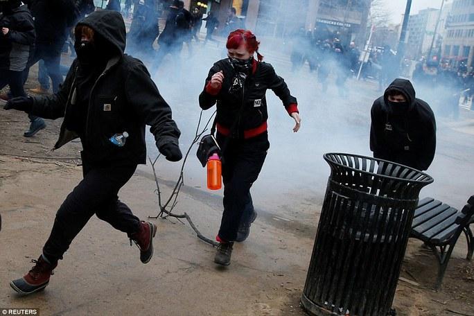 Nhóm biểu tình bỏ chạy khi cảnh sát sử dụng hơi cay. Ảnh: Reuters
