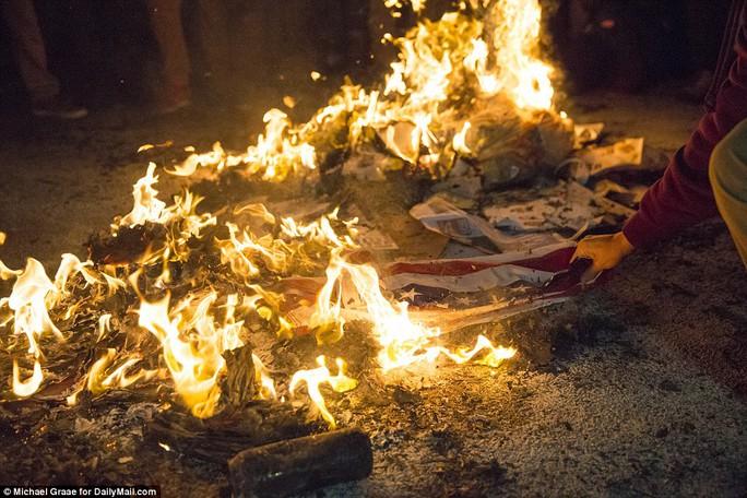 Cờ Mỹ bị đốt. Ảnh: Daily Mail