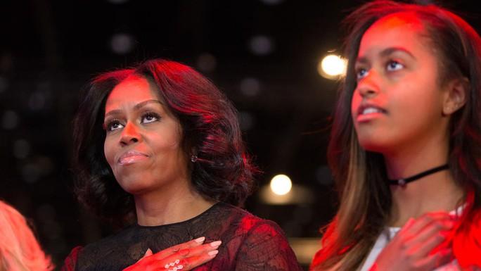Bà Michelle và con gái Malia đứng khi hát quốc ca. Ảnh: CHICAGO TRIBUNE