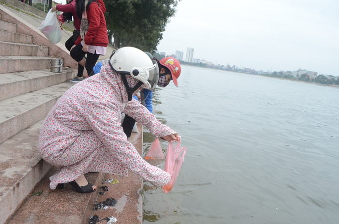 Tại hồ Linh Đàm, nhiều người đi thả cá chép tiễn Táo quân về chầu Thiên đình