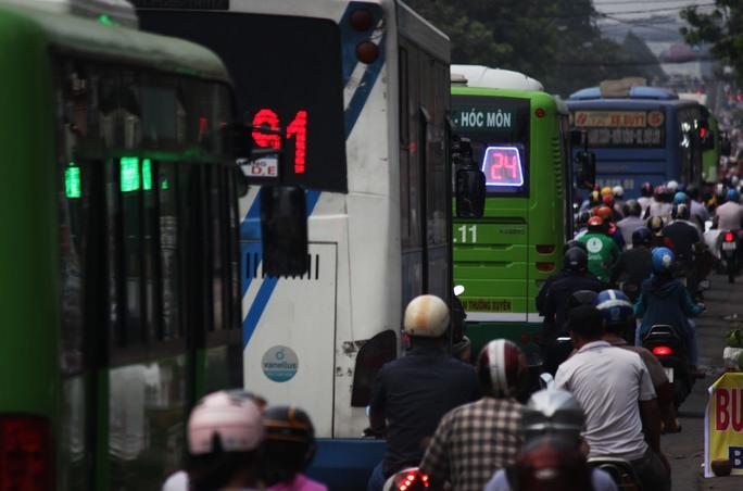 Xe buýt xếp thành hàng dài trong vòng vây của xe máy, bít kín toàn bộ con đường.